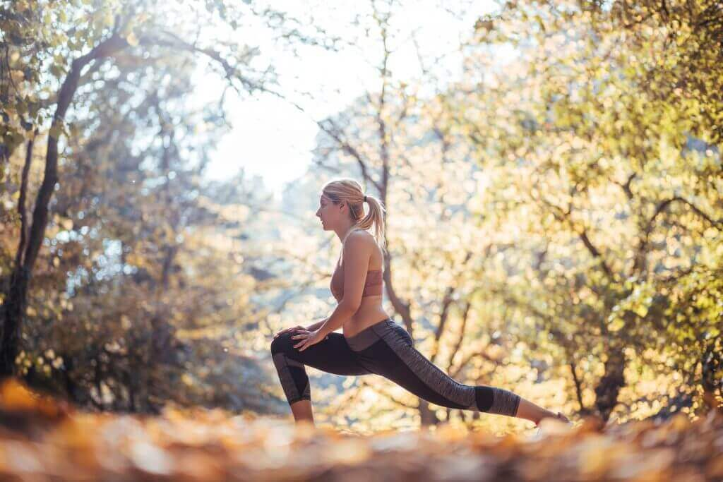 lady stretching in woods